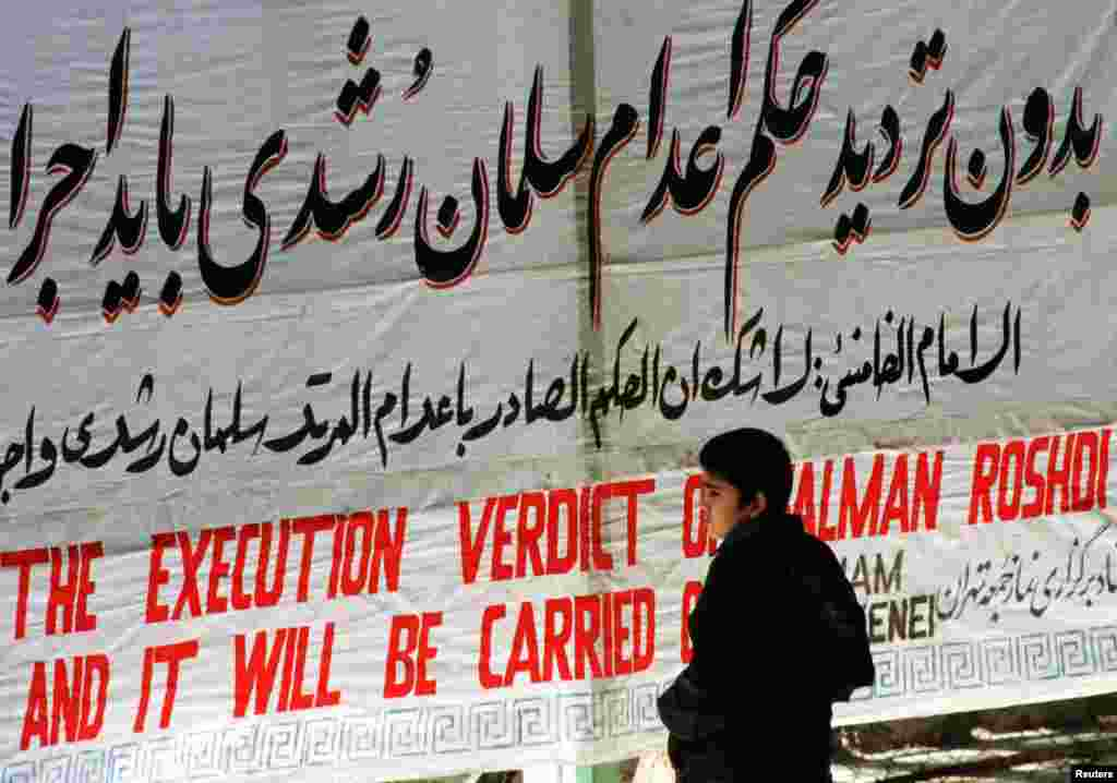 "A boy stands at Tehran University in February 2012 in front of a banner reading, ""The execution verdict of Salman Rushdi will be carried out."""
