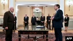 Алексіс Ципрас (п) складає присягу прем'єра перед президентом Каролосом Папульясом (л) у президентському палаці в Афінах, 26 січня 2015 року