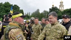 Ukrainian President Petro Poroshenko (right) awards a Ukrainian soldier in the eastern city of Slovyansk on July 8.