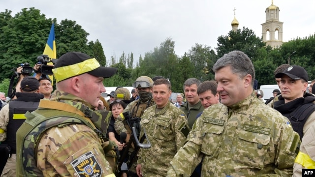 Ukrainian President Petro Poroshenko (right) awards a Ukrainian soldier in the eastern city of Slovyansk on July 8.