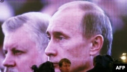 На величезному екрані в Кремлі — Миронов (л) і Путін (п) в той час, як вони слухають промову Медведєва, фото 2008 року