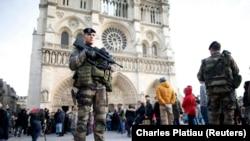 Вооруженные сотрудники безопасности стоят на площади перед собором Парижской Богоматери. Париж, 30 декабря 2015 года.