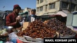 Уличный торговец в Афганистане продает финики перед Рамаданом рядом с рынком в Кабуле.