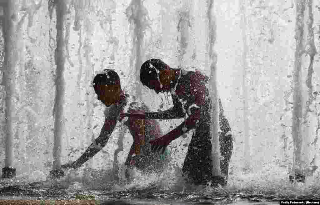 Boys cool themselves in a fountain during a hot summer day in central Minsk. (Reuters/Vasily Fedosenko)