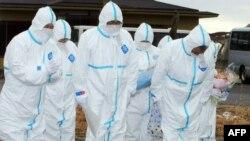 """Жители японского города Окума, пострадавшего от аварии на """"Фукусиме"""", предлагают безмолвные молитвы по погибшим людям. 11 марта 2012 года."""