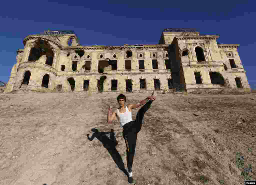 Abbas Alizada, who calls himself the Afghan Bruce Lee, poses in front of the destroyed Darul Aman Palace in Kabul. (Reuters/Mohammad Ismail)