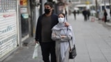 A couple walks in Enghelab Square in Tehran on March 26. Amid a deadly outbreak of coronavirus in Iran, alleged miracle cures and misinformation have spread online.