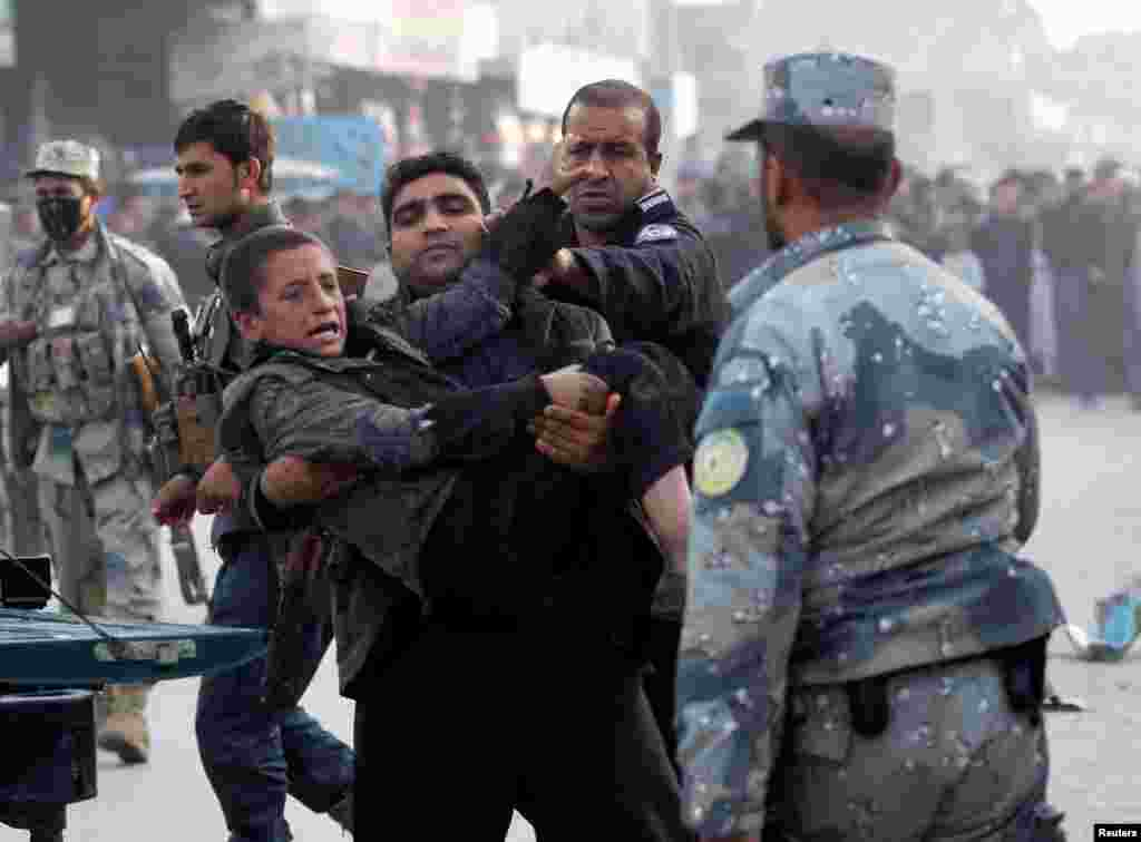 Afghan policemen carry an injured boy after a bomb blast in Jalalabad on February 1. (Reuters/Parwiz)