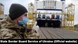 Український прикордонник координує прибуття громадян України, порт Чорноморськ, Одеська область, 6 квітня 2020 року
