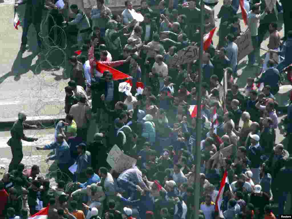 An Egyptian soldier tries to contain thousands of supporters of President Hosni Mubarak pushing into Tahrir Square.