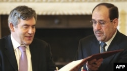 "British Prime Minister Gordon Brown (left) and his Iraqi counterpart Nuri al-Maliki sign a bilateral ""Joint Declaration of Friendship, Partnership, and Cooperation"" in London on April 30."