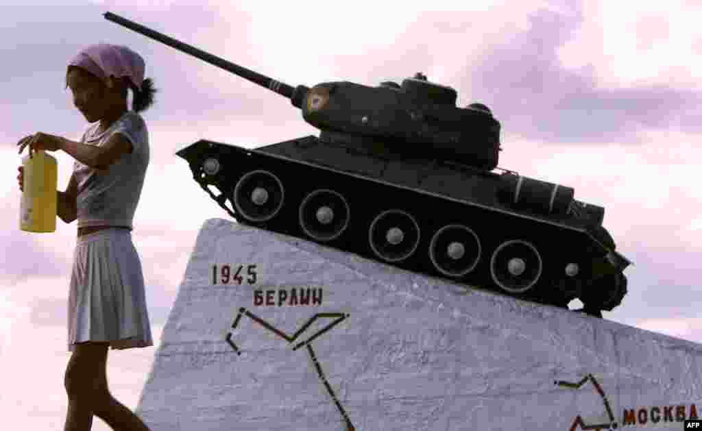 Муғулистон, духтараке дар назди танки шӯравӣ шарбат менӯшад, Улан-Батор. 4 июли соли 2000.