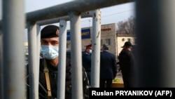 Сотрудник сил безопасности на блокпосту между закрытым на карантин Алматы и Алматинской областью. 19 марта 2020 года.