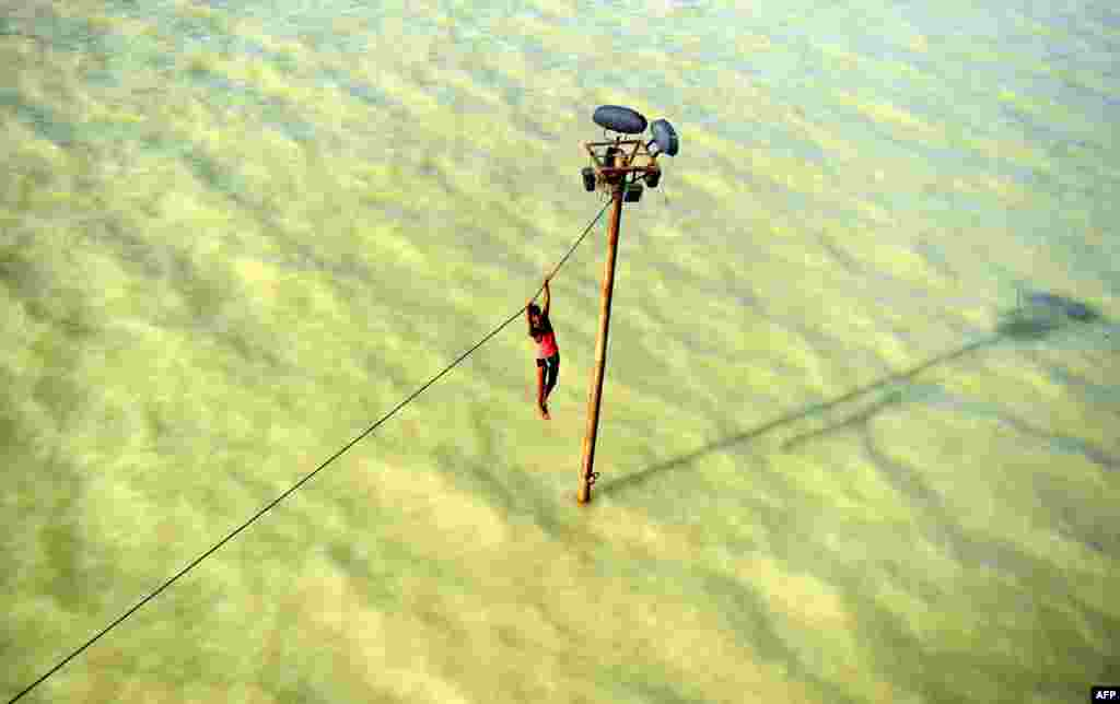 A youth dangles from a power line before diving into the floodwaters of an overflowing Ganges River in Allahabad, India. (AFP/Sanjay Kanojia)