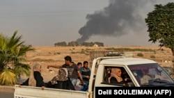 Беженцы покидают курдский город Рас-эль-Айн вблизи границы, обстреливаемый турецкими войсками. 9 октября 2019 года