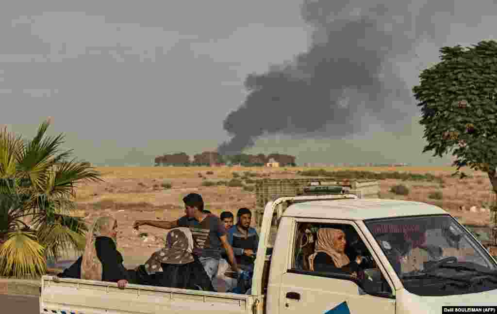 Civilians ride a pickup truck as smoke billows following Turkish bombardment on Syrian town of Ras al Ain, October 9, 2019.