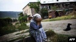 Жена од Грузија плаче на местото каде била уништена зградата во која живеела.
