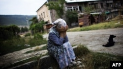 A Georgian woman cries at the entrance of her destroyed building in a battered neighborhood in Gori on August 23, 2008.