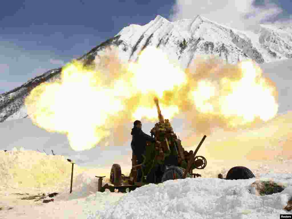 A member of an emergency services special unit fires a shell toward the upper slopes to clear snow buildup above the Transcaucasian highway some 110 kilometers from the southern Russian city of Vladikavkaz on March 13. Avalanches are a constant threat on the road, which is the only route connecting Russia to the Georgian separatist region of South Ossetia. Photo by Kazbek Basayev for Reuters