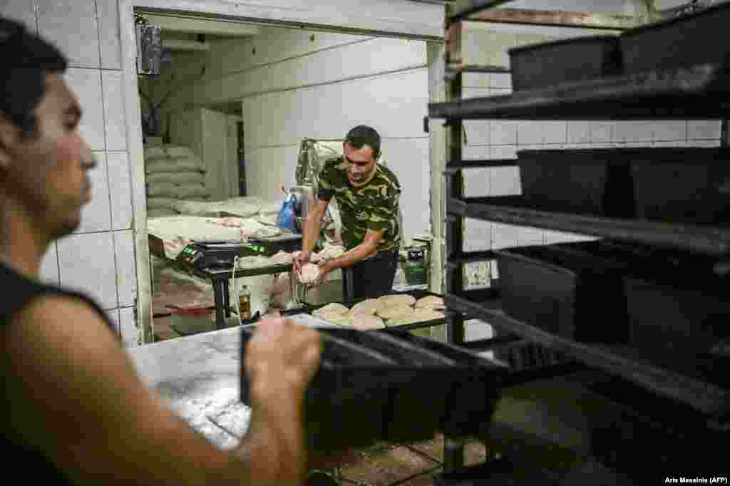 A dolgozók előkészítik a tésztát a sütésre.