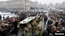 Архива - Луѓе во Украина учествуваат во погребна церемонија на војници.