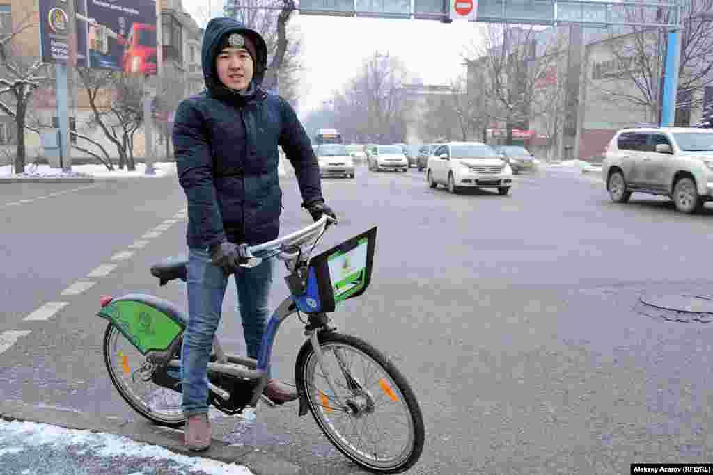 Этого молодого человека, чтобы пообщаться с ним, пришлось догонять. Его зовут Тлек. Он студент КазНПУ. Но в данный момент он ехал не на занятия, а на работу. Зимой на велосипеде ездит почти всегда. Своего велосипеда у него нет, и он пользуется прокатным. Как студент он платит за пользование только 5 тысяч тенге в год. О существующей инфраструктуре он сказал, что велодорожек маловато. Но он ездит и по выделенным полосам для общественного транспорта (ПДД это разрешают). Об акции «Зимой на работу на велосипеде» он узнал от репортера Азаттыка.