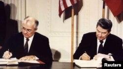 Совет одағының жетекшісі МихаилГорбачев (сол жақты) және АҚШ президентіРональдРейган ядролық келісімге қол қойып жатыр. Желтоқсан айы, 1987 жыл.