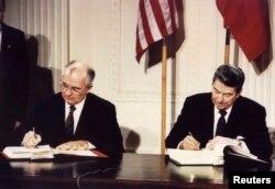 Президент СССР Михаил Горбачев и президент США Рональд Рейган подписывают договор о сокращении ядерного оружия средней дальности. Вашингтон, 8 декабря 1987 года.