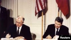Президент США Рональд Рейган (П) та СРСР Михайло Горбачов (Л) підписують Договір про ліквідацію ракет середньої і малої дальності, 8 грудня 1987