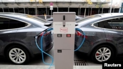 Makina elektrike të kompanisë Tesla, duke rimbushur bateritë në Berlin.