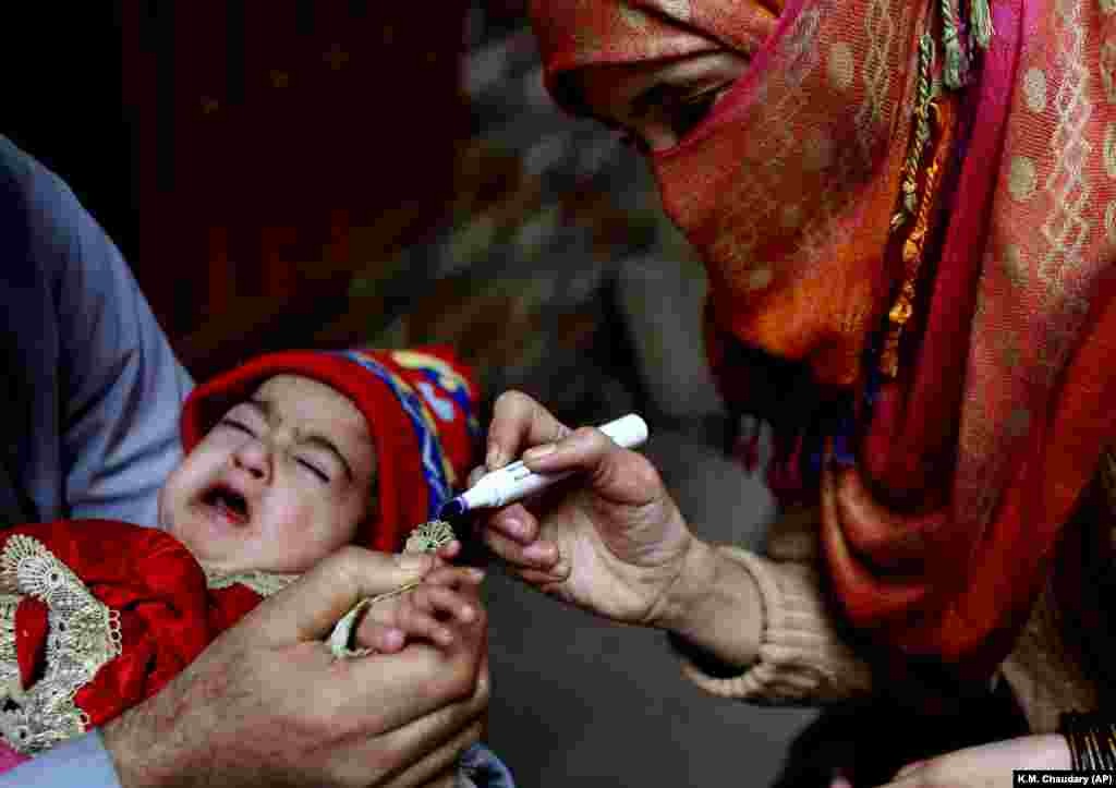 A health worker marks a finger after giving a polio vaccination to a child in Lahore, Pakistan. Despite a steady rise in coronavirus cases, Pakistan on January 11 launched a five-day vaccination campaign against polio amid tight security, hoping to eradicate the crippling children's disease this year. (AP/K.M. Chaudary)