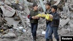 کودکان در منطقهای از حلب که در کنترل شورشیان است، کارتنهای بیسکویت را به خانه میبرند