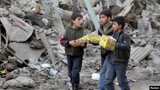 Boys carry boxes of biscuits near rubble of damaged buildings in Aleppo.