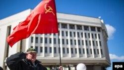 Қырымдағы референдум нәтижесі жария болған соң парламент алдында бұрынғы СССР туын ұстап тұрған адам. Симферополь, 17 наурыз 2014 жыл.