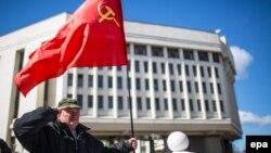 Чоловік із радянським прапором біля будівлі кримського парламенту, 17 березня 2014 року