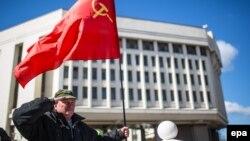 Крым парламентинин алдында бир киши СССрдин желегин көтөрүп турат. Симферополь, 17-март, 2014.