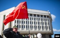 Мужчина держит советский флаг напротив здания парламента после окончания референдума в Симферополе. 17 марта 2014 года.