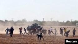 Участники акции протеста в Сурудже на сирийско-турецкой границе забрасывают камнями БТР, 7 октября 2014 года.