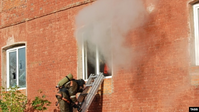 A firefighter stands on a ladder by a window of a garment factory on fire in the town of Yegoryevsk, southeast of Moscow, on September 11.