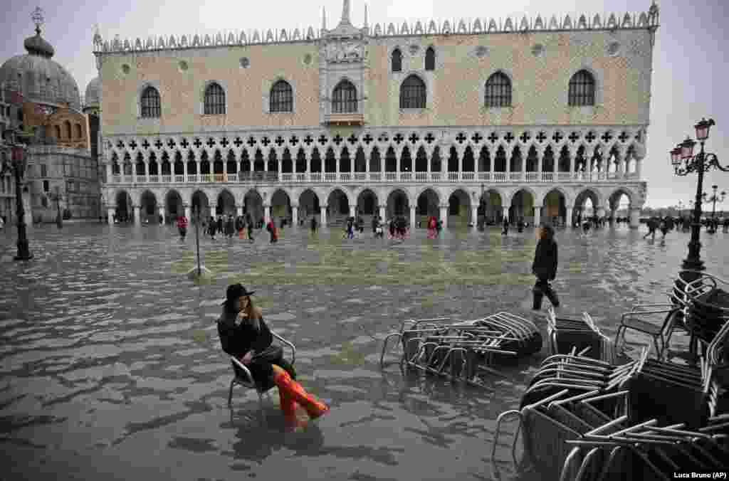 A woman sits in a chair in a flooded St. Mark's Square in Venice. The high-water mark hit 187 centimeters, meaning more than 85 percent of the city was flooded. The highest level ever recorded was 194 centimeters during infamous flooding in 1966. (AP/Luca Bruno)