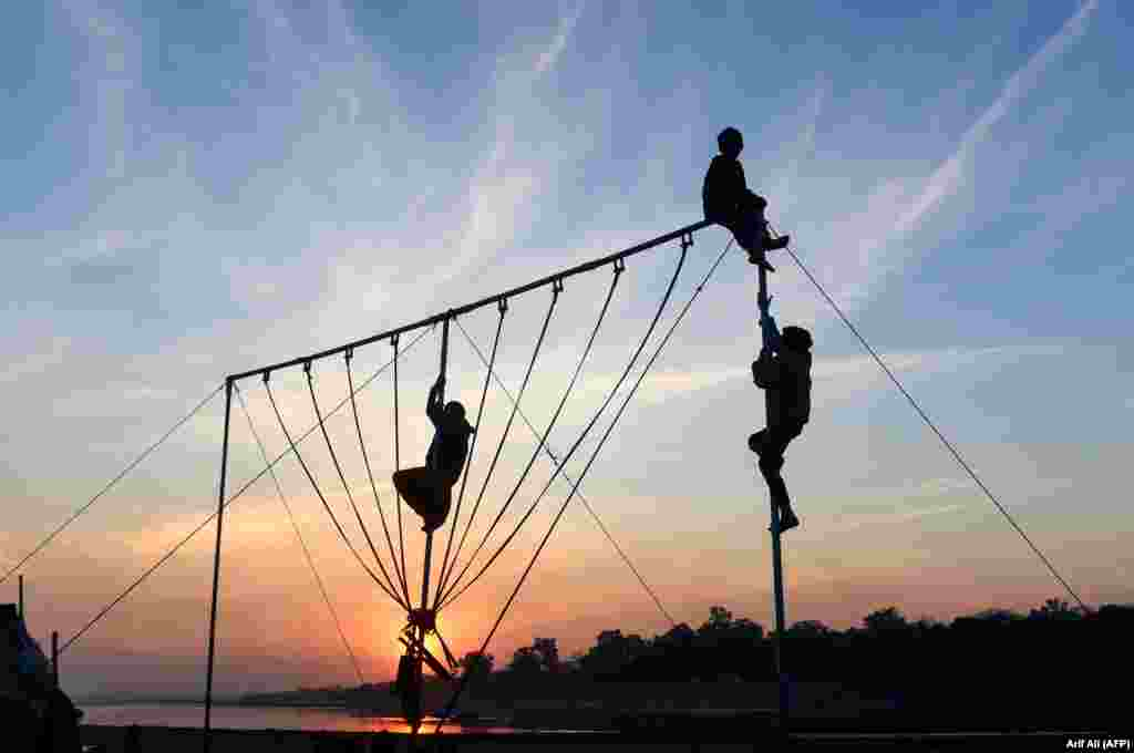 Pakistani children play on swings at sunset in Lahore. (AFP/Arif Ali)