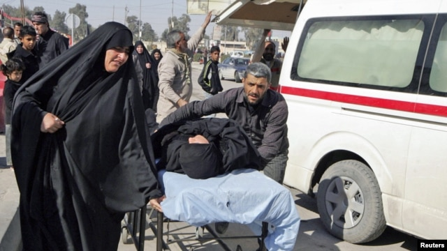 Residents wheel a stretcher carrying a wounded woman after a bomb attack targeted Shi'ite pilgrims commemorating a religious ceremony in Karbala.
