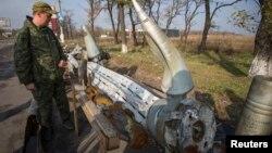 یکی از جداییطلبان به بقایای مواد انفجاری که ساکنان شرق اوکراین میگویند نیروهای دولتی از آنها استفاده کردهاند، نگاه میکند