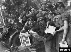 عکسی به تاریخ ۲۰ مه ۱۹۴۵، سربازان کانادایی خبر شکست کامل ارتش نازی را در روزنامه میخوانند