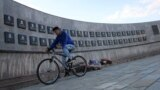 Kosovo -- A youth cycles past the memorial to the victims of the Recak massacre, where forty-five ethnic Albanians were killed by Serbian forces in January 1999, in the village of Recak, September 22, 2016