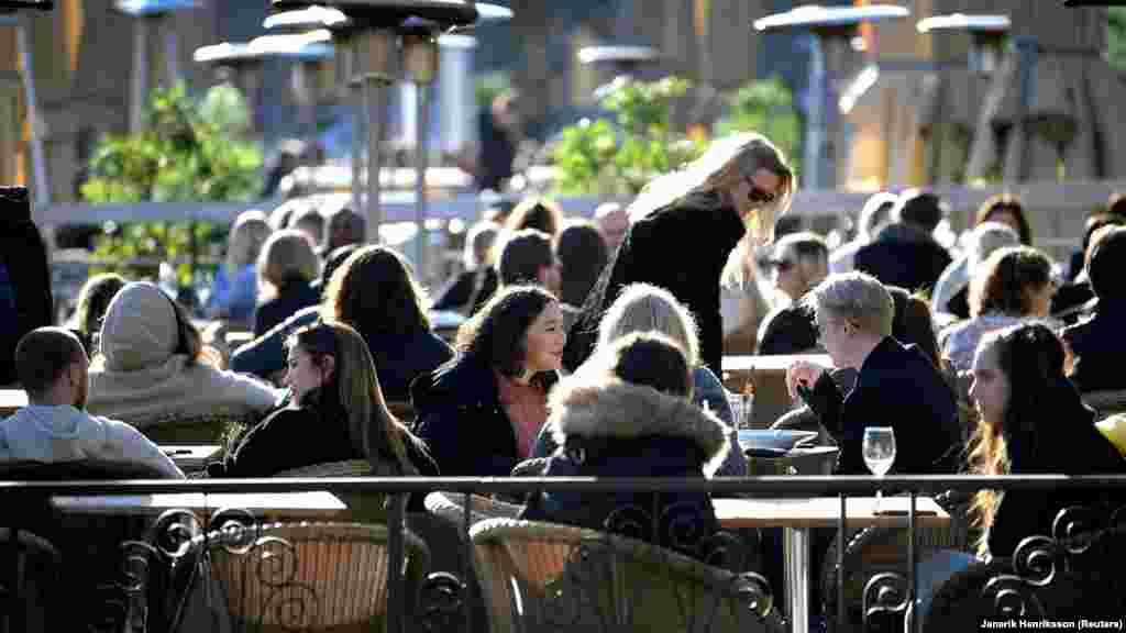 Көктем шуағына малынып, мейрамханада тамақтанып отырған Стокгольм тұрғындары. 26 наурыз 2020 жыл.