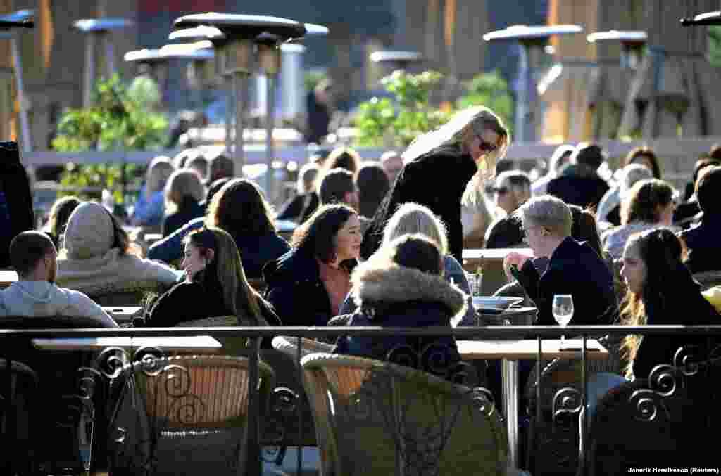 Suedezët shijojnë rrezet e diellit të pranverës në një restorant në natyrë në Stokholm, më 26 mars.