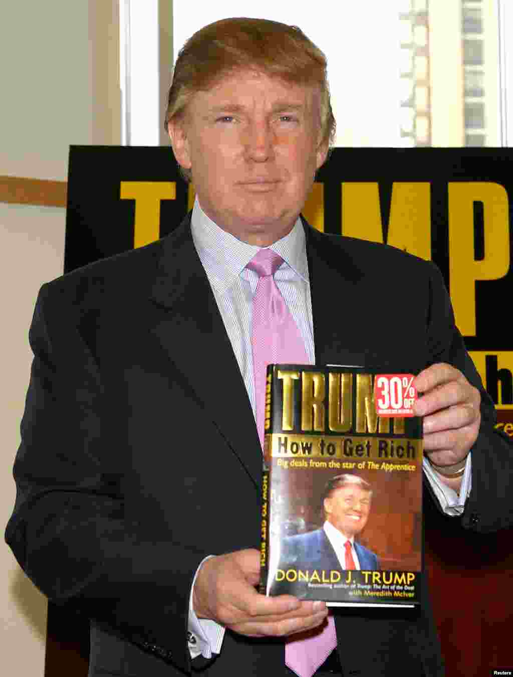 Trump holds a copy of his book, How To Get Rich, in 2004. His 1987 book, The Art Of The Deal, was a best seller that increased his fame.