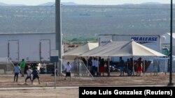 Дети задержанных мигрантов, играют в футбол в лагере на границе США