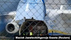 Работници растовараат авион со медицинска опрема од Кина за Полска, април 2020